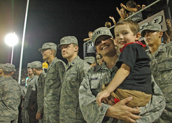 Photo by: Isaac Babcock - U.S. Air Force Capt. Abbi Johnson watches the UCF football game with son Spencer, 4, on Sept. 10.