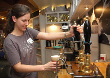 Photo by: Isaac Babcock - Bartender Amber Leenstra pours an Old Thumper at the Shipyard Emporium during the Maine-based brewery's grand opening on Friday night, Jan. 29, on Fairbanks Avenue. The market and brewhouse offered $2 beers and free samples o...