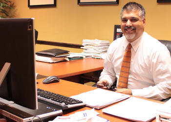 Photo by: Amanda Georgi - Ivan Valdes sits at his desk on April 13 at his Maitland financial firm. He'll be sworn in to the Maitland City Council on Monday, April 25.