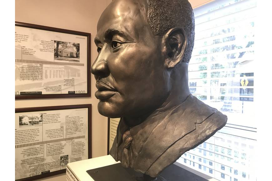 A bust of Martin Luther King, Jr. sits between a timeline of the Winter Park African American community spanning the 20th century to present day. The timeline documents notable local and national events.
