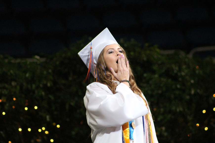 Graduating senior Ashley Lloyd, a recipient of the Disney Dreamers & Doers Award, does the Warrior howl shortly after giving her speech.