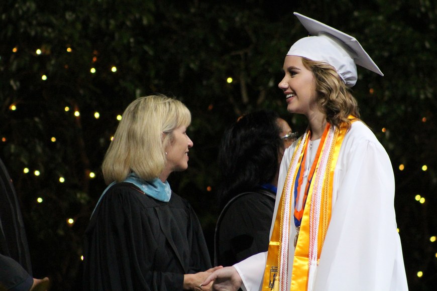 Caroline Dunham smiles giddily as she walks across the stage shaking hands with school faculty.