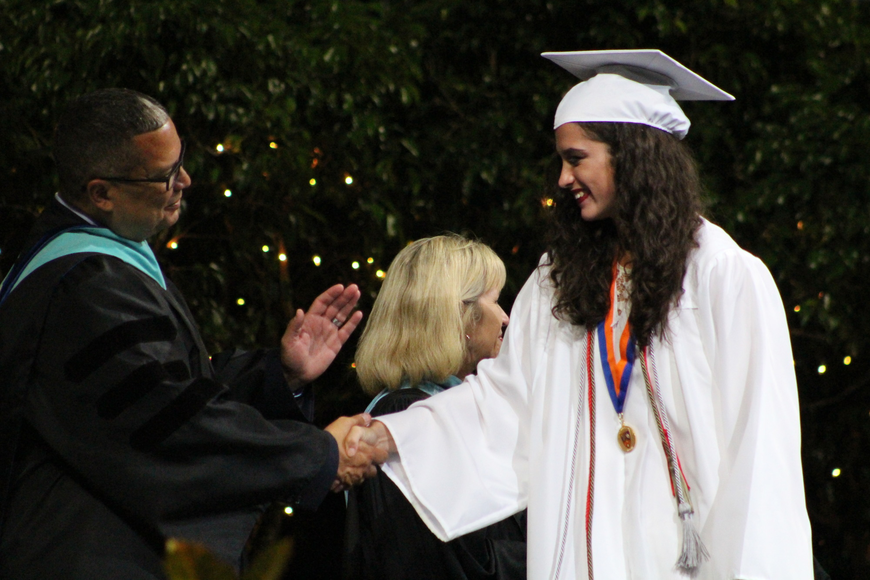 Graduating senior Eloisa Gonzalez happily shakes hands with West Orange High teachers and administrators.