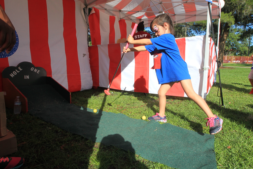 Gabriella Desouza, 4, plays a golf game during Winter Park's Fourth of July Celebration.