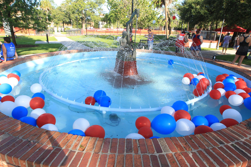 Red, white, and blue balloons float around in the fountain in Central Park as festivities start up.