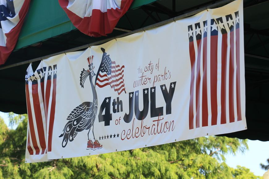 A banner celebrating Winter Park's Fourth of July Celebration hangs above the stage in Central Park.