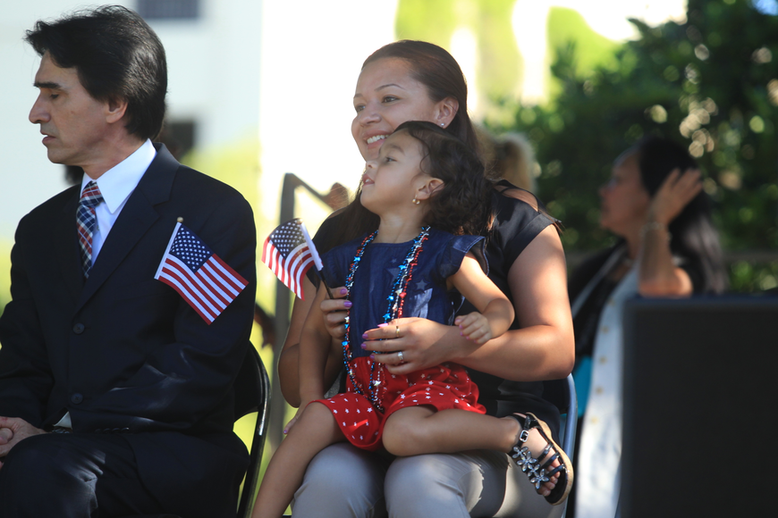 Lina Penagos, from Colombia, holds her daughter, Maya Perez, during a naturalization ceremony held in downtown Winter Park.