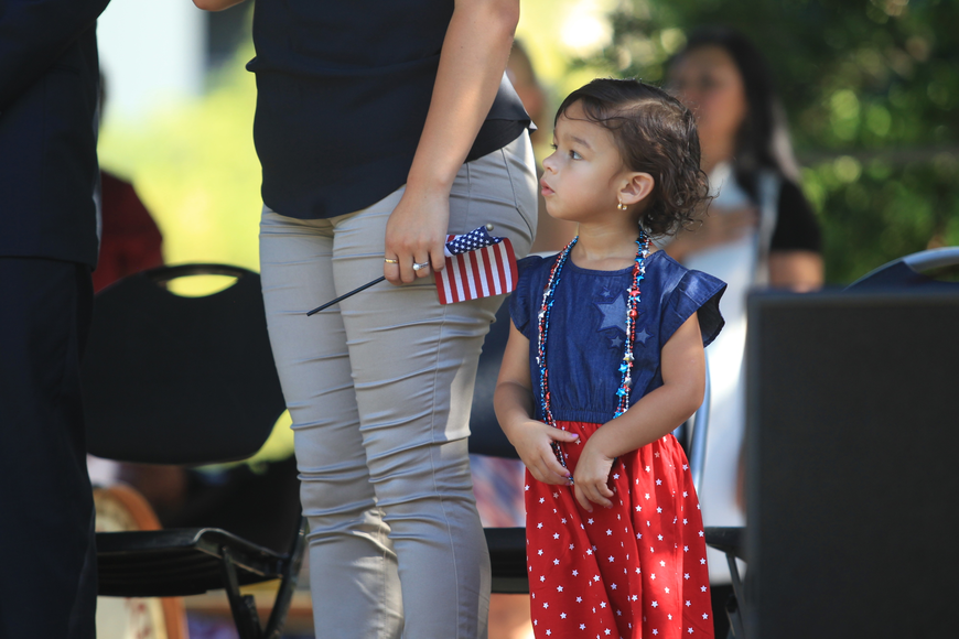 Maya Perez looks on as her mother, Lina Penagos, right, takes an oath during the naturalization ceremony held in downtown Central Park.
