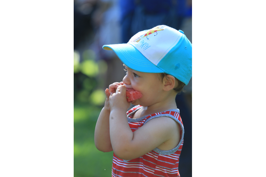 August Moore, 1, tears into a slice of watermelon as he enjoys a fun morning.