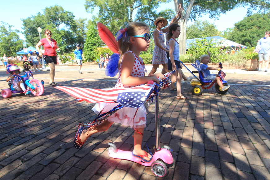 Alice Tunnock-Huff, 4, rides down Park Avenue as she and other children participate in a patriotic bicycle parade.
