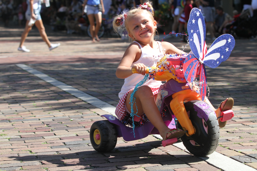 With a big grin on her face, Kendall Matthews, 4, rides down Park Avenue as she participates in a Fourth of July bicycle parade.
