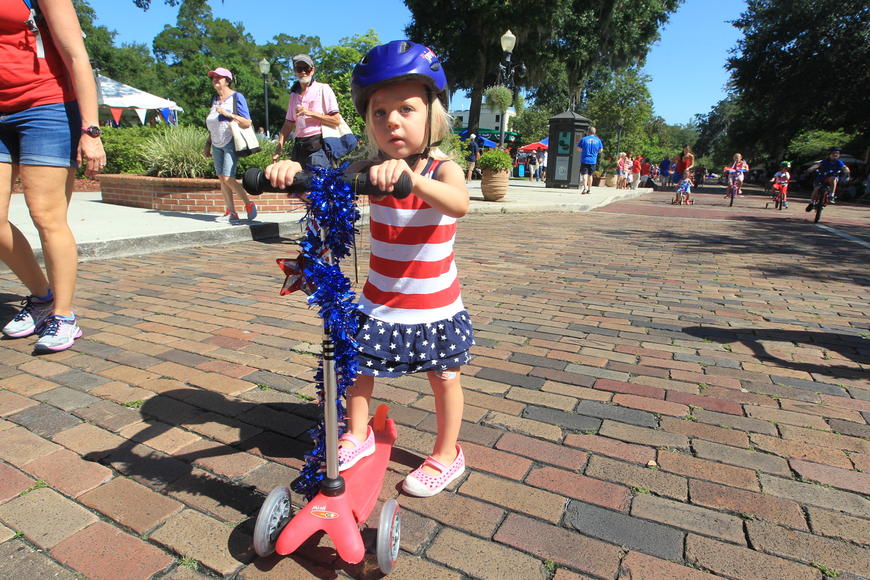 Lily McCormack, 2, pushes herself along Park Avenue during a children's bicycle parade.