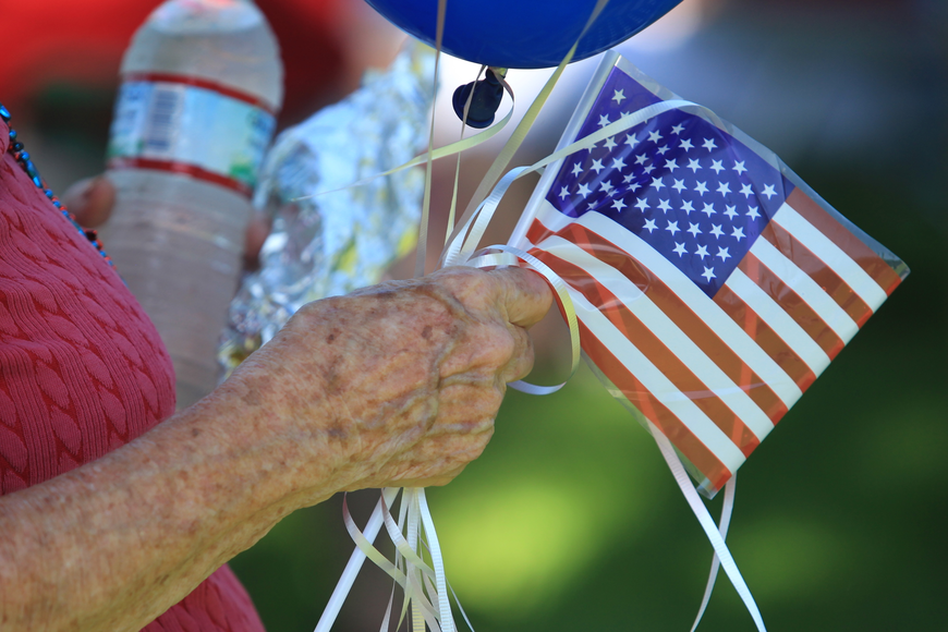 A woman holds balloons and a small American flag as she takes in Winter Park's Fourth of July Celebration.