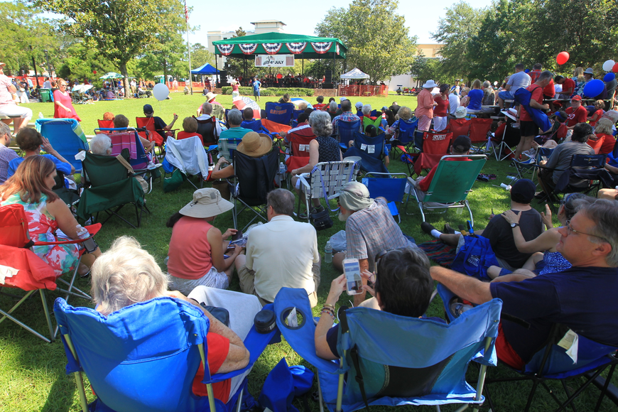 A crowd of onlookers enjoy a sunny morning and live music during Winter Park's Fourth of July Celebration.