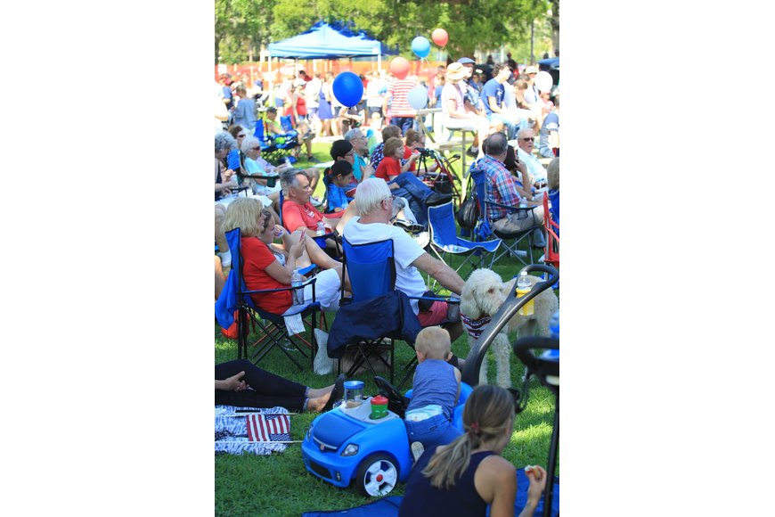 A large crowd enjoy a sunny morning and live music during Winter Park's Fourth of July Celebration.