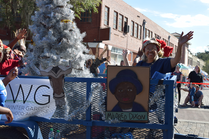 Members of the East Winter Garden Neighborhood Alliance greet parade attendees  and thow candy from its float.