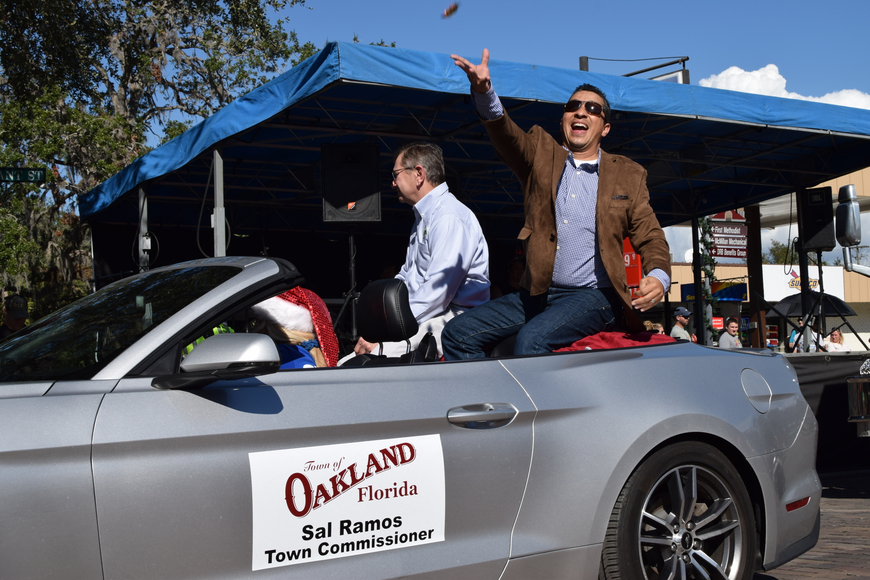 Town of Oakland Commissioner Sal Ramos gleefully throws candy to parade participants.