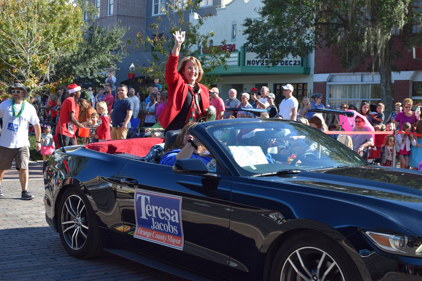Orange County Mayor Teresa Jacobs rolls in perched on the back seat of a sleek black Mustang.