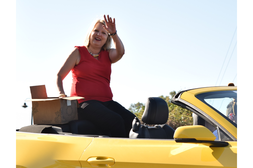 Orange County School Board District 7 member Christine Moore waved from atop a yellow convertible.