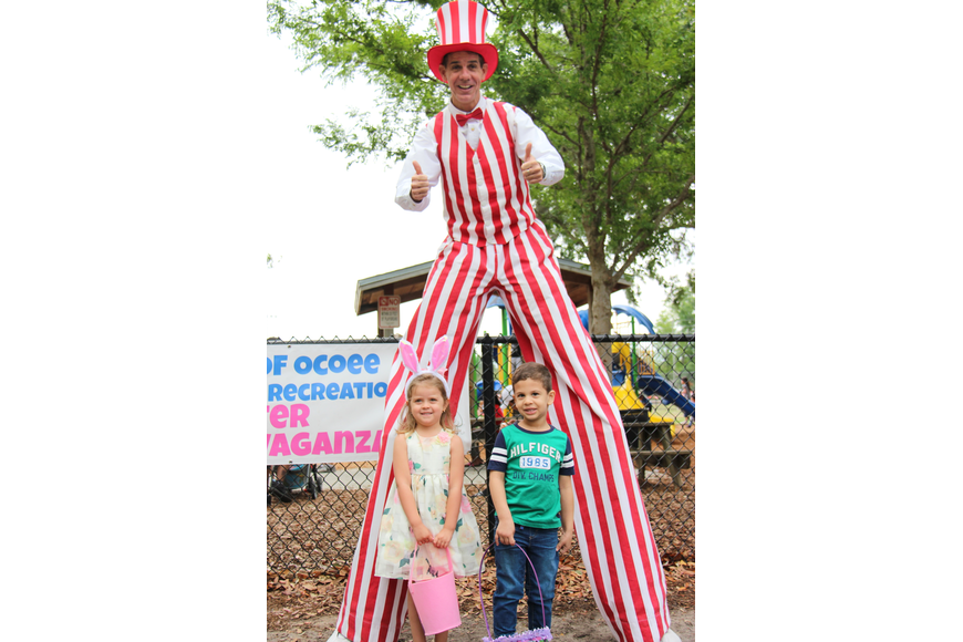 Stilt-walker Mike Weakley greeted guests and posed for a photo with Stella Dores, left, and Lucca Araujo.