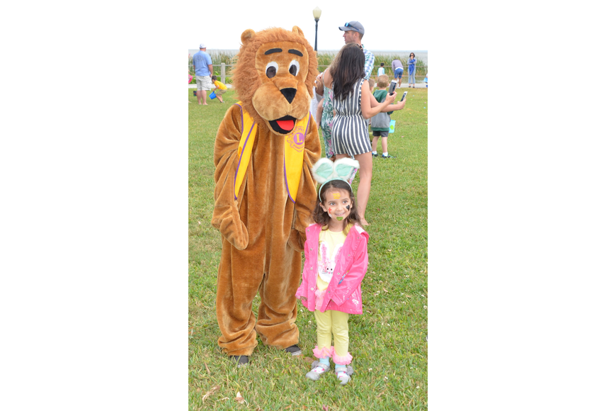 Alexandra Sheffer, 4, poses with the Lions Club mascot before the egg hunt begins.