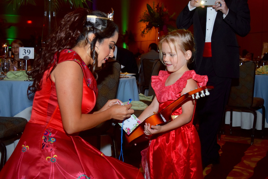 Audrey Stagg holds Elena of Avalor's guitar as she gets her autograph book signed.