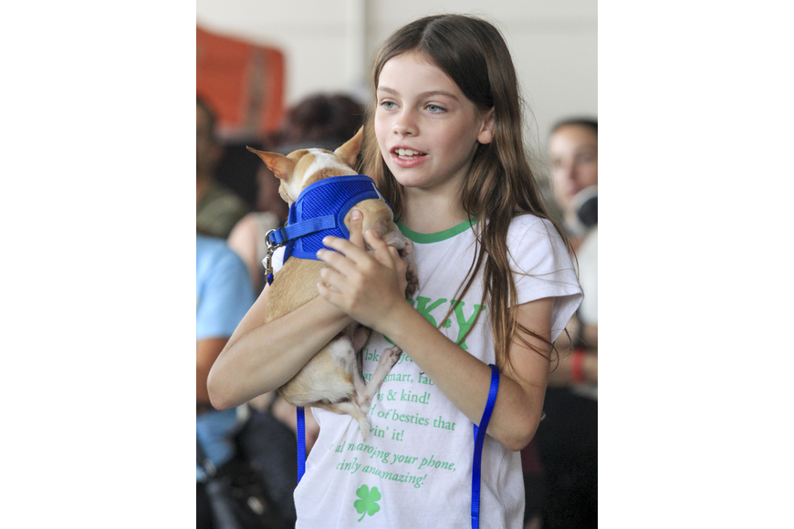 Madison Barger holds Lucky, her rescued dog, after he finished his race.