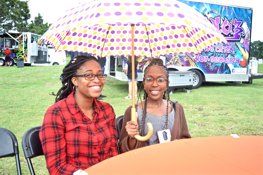 Alicia Gardiner and Laura Veillard sheltered from the rain under their large umbrella.