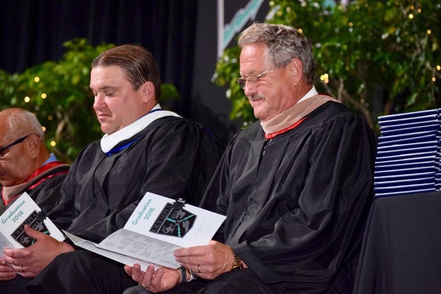 District 44 State Rep. Bobby Olszewski and Windermere Mayor Gary Bruhn look at their graduation programs.