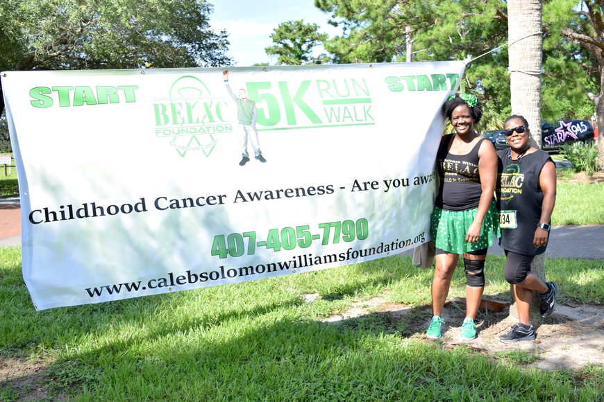 Amperell Williams and Temeka Harris proudly posed by the Caleb Solomon Williams BELAC Foundation banner.