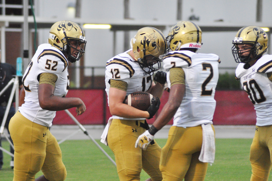 Jake Kiefer, center, celebrates with teammates after scoring the first touchdown of the game.