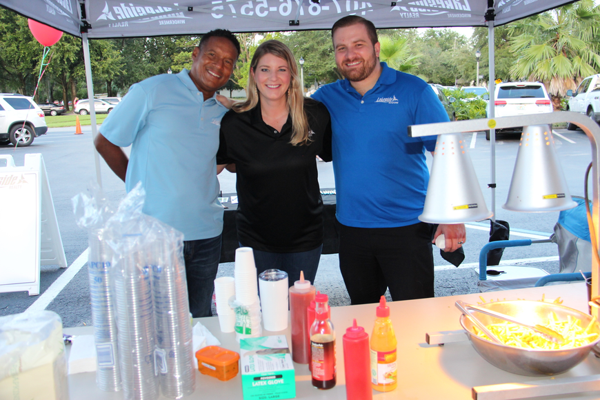 W. Channing Harrison, left, Jessica Long and Francisco Orchilles of Lakeside Realty served up French fries to hungry strollers.