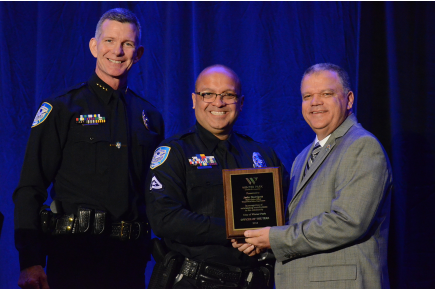 Master Police Officer Javier Rodriguez, center, was recognized as Officer of the Year by Police Chief Michael Deal and City Manager Randy Knight.