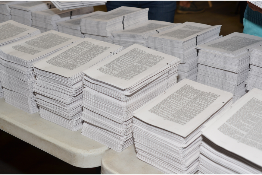 Batches of Bible pages to be collated.