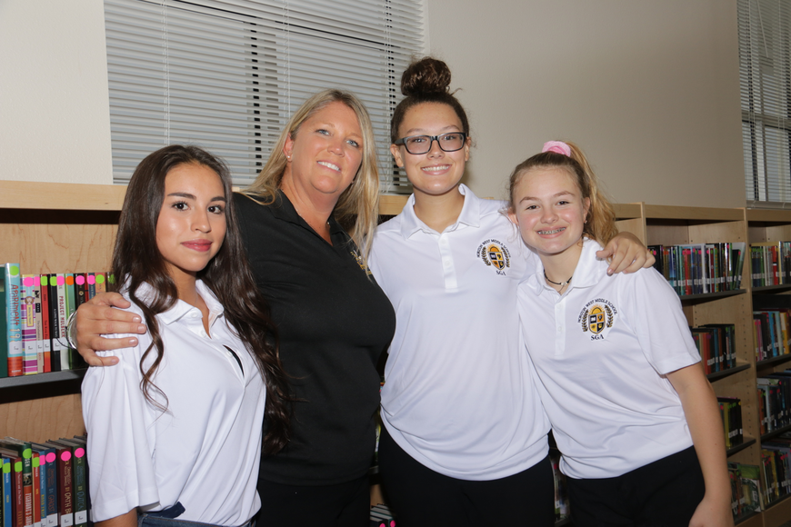 Principal Michelle Thomas, center-left, caught up with eighth-grade student government members Coudia Ospina, 14; Ayden Newsom, 13; and Samantha Zotti, 12, at the school's media center. Student government members were tour guides.