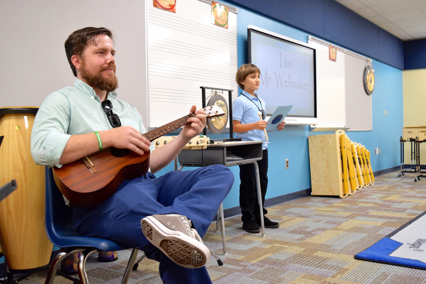 Music teacher Kevin Wellmaker played ukulele alongside his student helper.