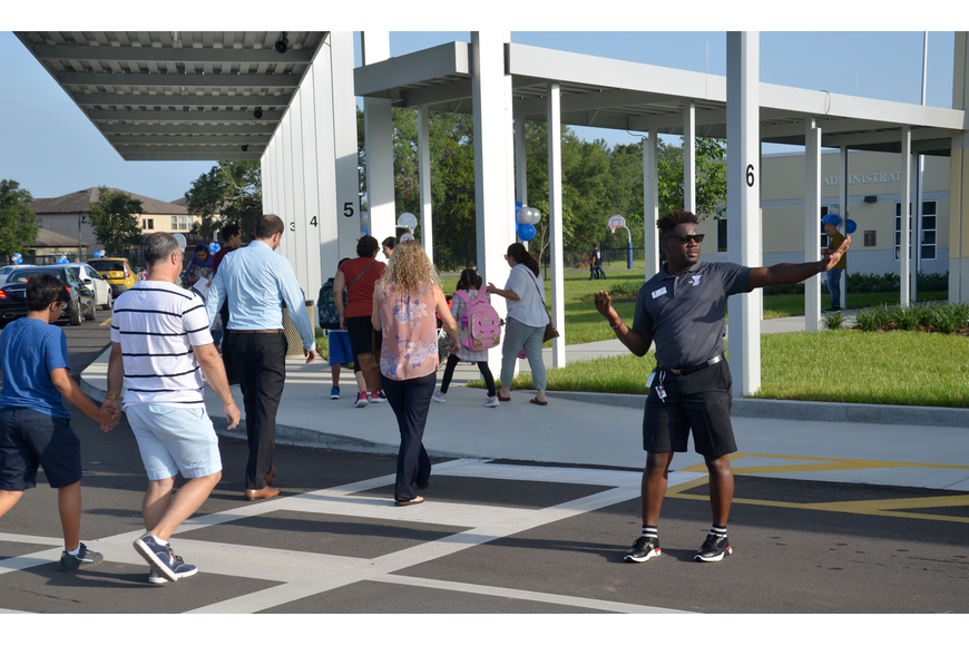 Junior ChaCha, of the YMCA of Central Florida, kept the car line moving smoothly in the morning during the first day of school rush at Castleview Elementary School.