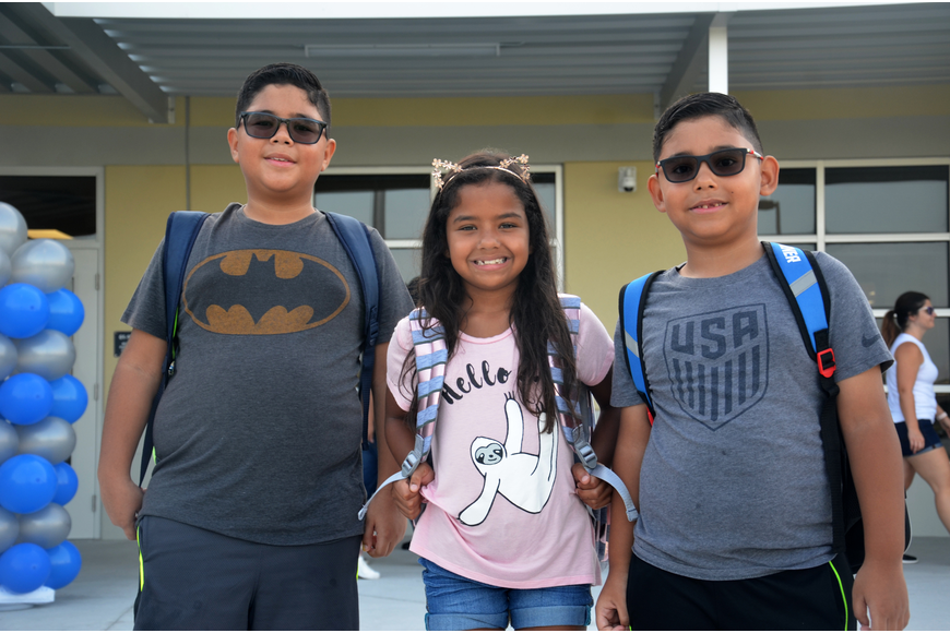 Students Nicolas Prato, Isabella Robles and Guillermo Prato stopped in front of their new school to snap a photo.