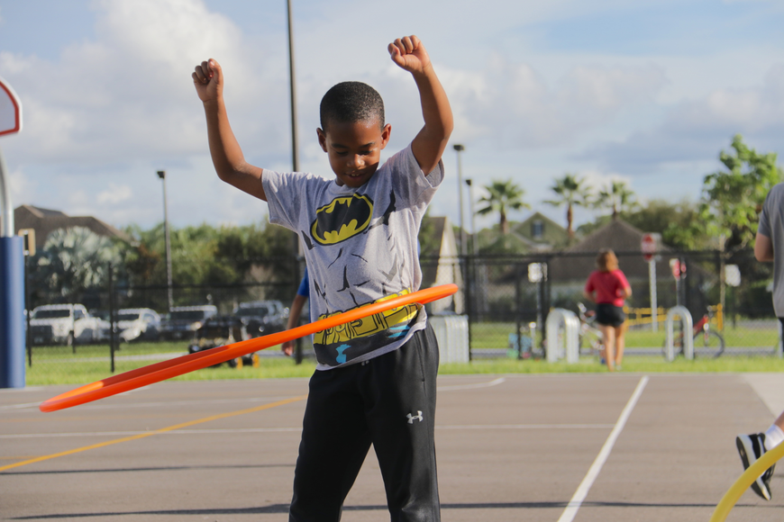 Third-grader Dion Colbourne took a break from playing basketball to play with a hula hoop.