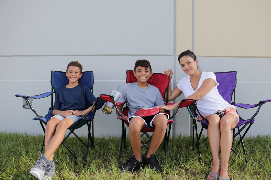 The Enriques — fourth-grader Kristopher; sixth-grader Kemren and their mom, Emely — set up their chairs in the shade to beat the heat.