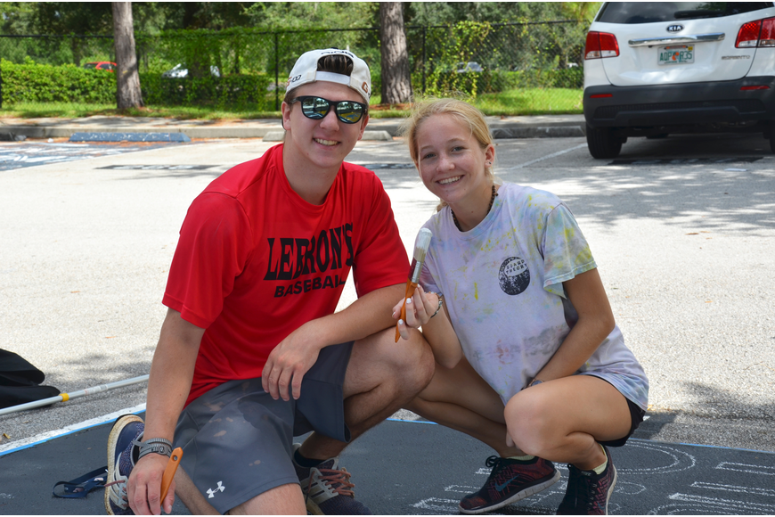 Cody Elliott lent a hand to senior Amelia Dickinson by painting Dickinson's parking spot at Olympia High School Saturday.