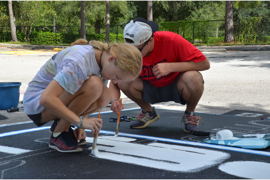 "Cody Elliott and Amelia Dickinson paint Dickinson's parking space with the sign from the television show, ""The Office."""