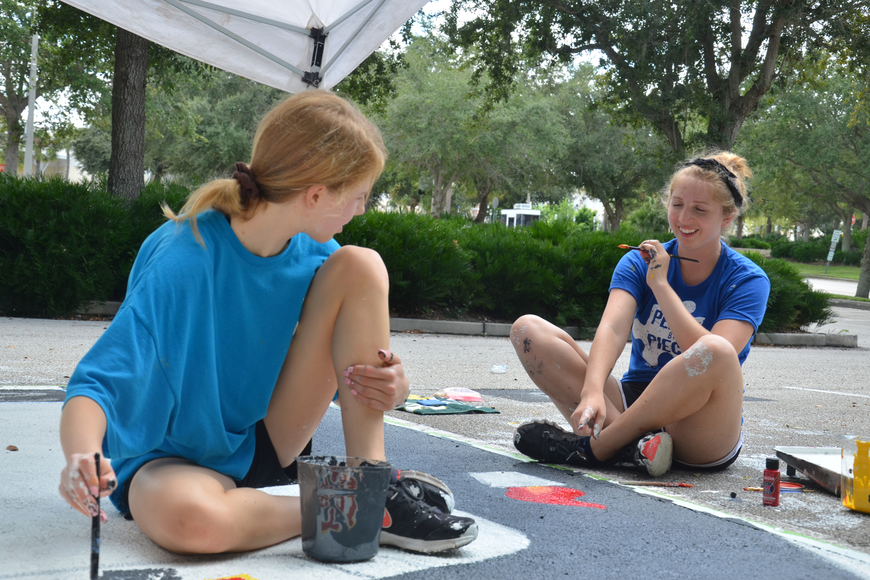 "Sophomore Genevieve Wheeler helped senior Jenna Morrison paint her spot Saturday morning. The design for the spot was a play on the sign from, ""Jurassic Park,"" which read, ""Welcome to Senior Year."""
