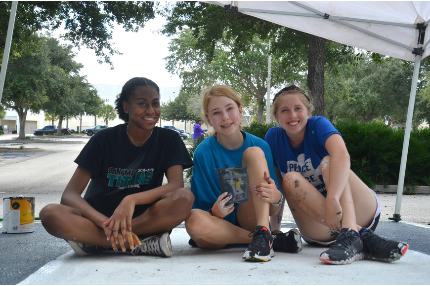 Senior Kaayin Griffin, sophomore Genevieve Wheeler and assisted senior Jenna Morrison with her parking spot painting.