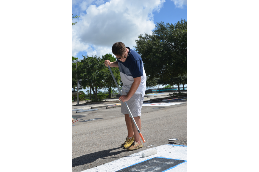 "Christian Morin started painting early in the spot for his girlfriend, senior Gabriela Mercado who was taking the SAT Saturday morning. The parking spot will be the first page of sheet music for the song, ""Lux Arunque."""
