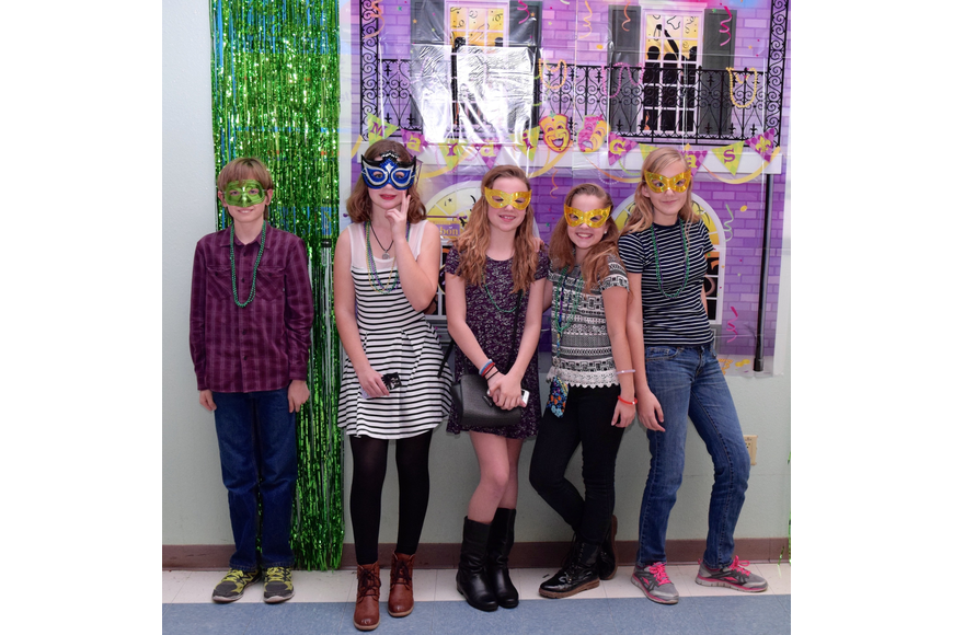 Students show off their masks in front of a Mardi Gras-themed backdrop.