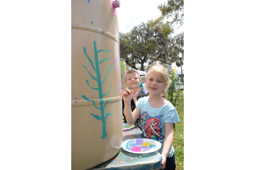 Samantha and Cameron Hannon, both 6, paint a rain barrel.