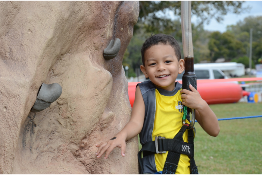 Tyler Burbank, 3, braves the rock-climbing wall.