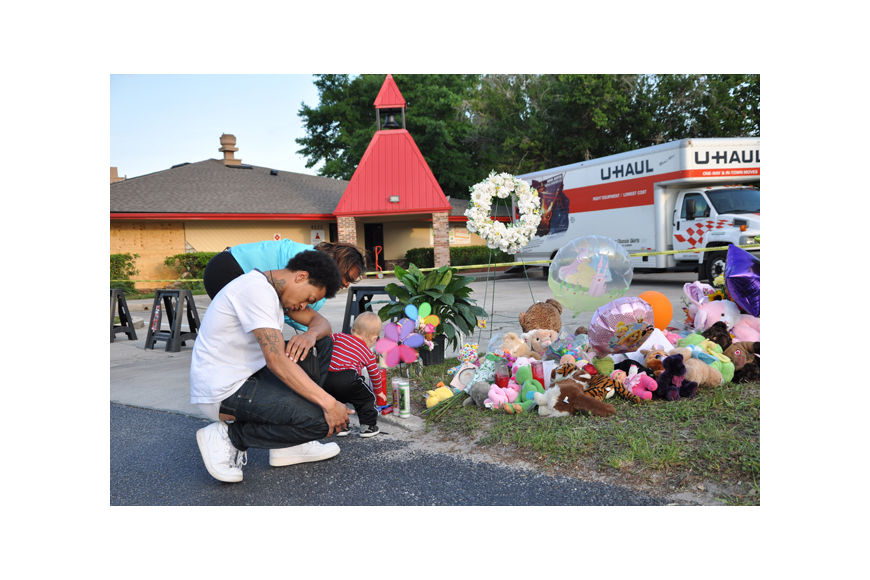 Photo by: Tim Freed - Well-wishers pray for victims of a crash that killed a toddler and injured 13 other children on April 9. The driver who allegedly caused the wreck had a long criminal history.