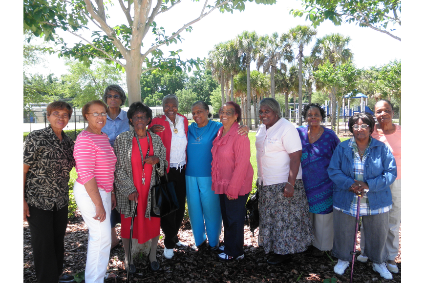 Photo by: Brittni Larson - The grandmothers pose after their meeting at the Rock Lake Community Center in Orlando on April 26. Yvonne Friend, far left, and Rounette Fulse, fifth from right, have both helped raise their children's children.